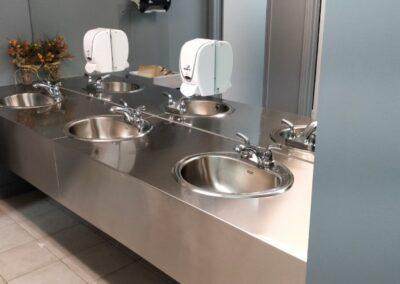 Comptoir de salle de bain publique en acier inoxydable.